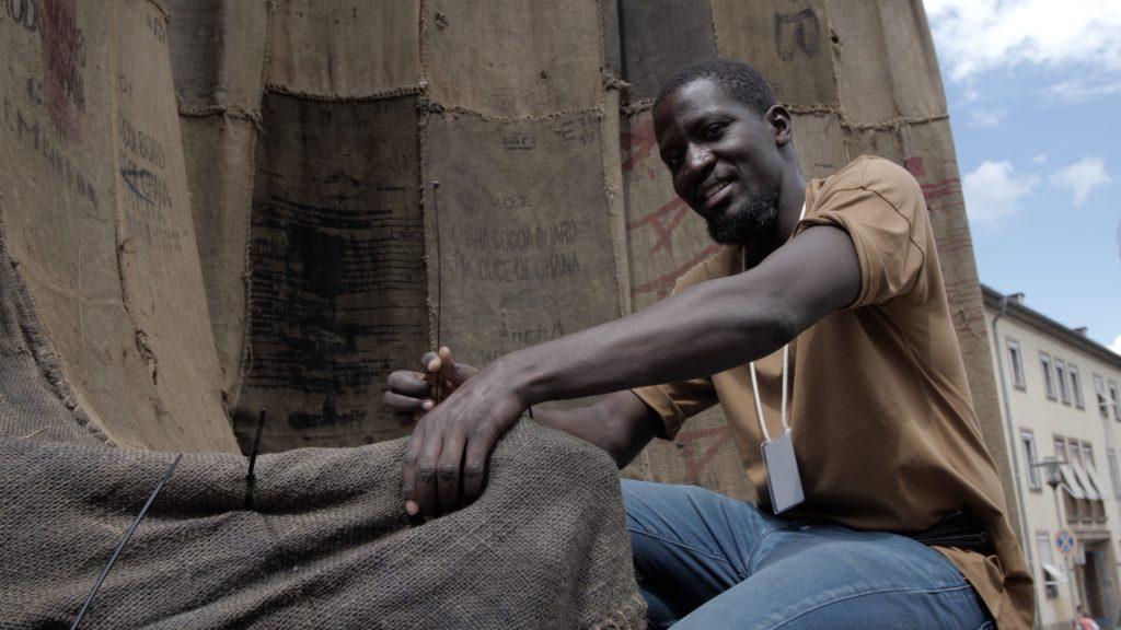 Ibrahim Mahama beim Fertigstellen seiner Arbeit