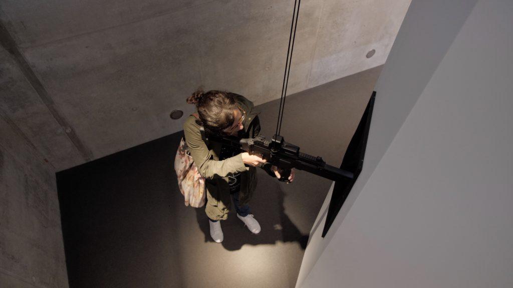 Ein G36 Maschinengewehr von Heckler und Koch in den Händen der documenta Besucher*innen